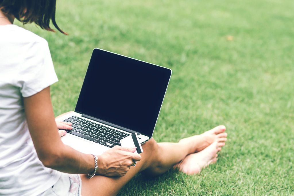 Bild zeigt das MacBook Pro auf dem Schoß einer Frau mit einer Kreditkarte.