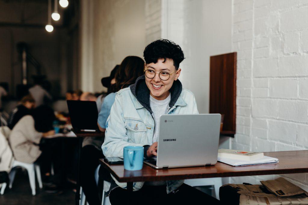 lächelnder Mann sitzt und benutzt Samsung Laptop in der Nähe von Menschen