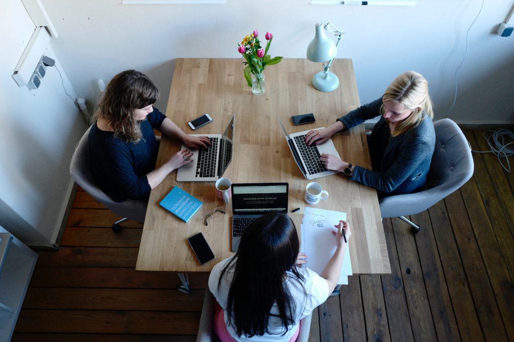 drei Frauen, die am Tisch sitzen und Laptops benutzen.