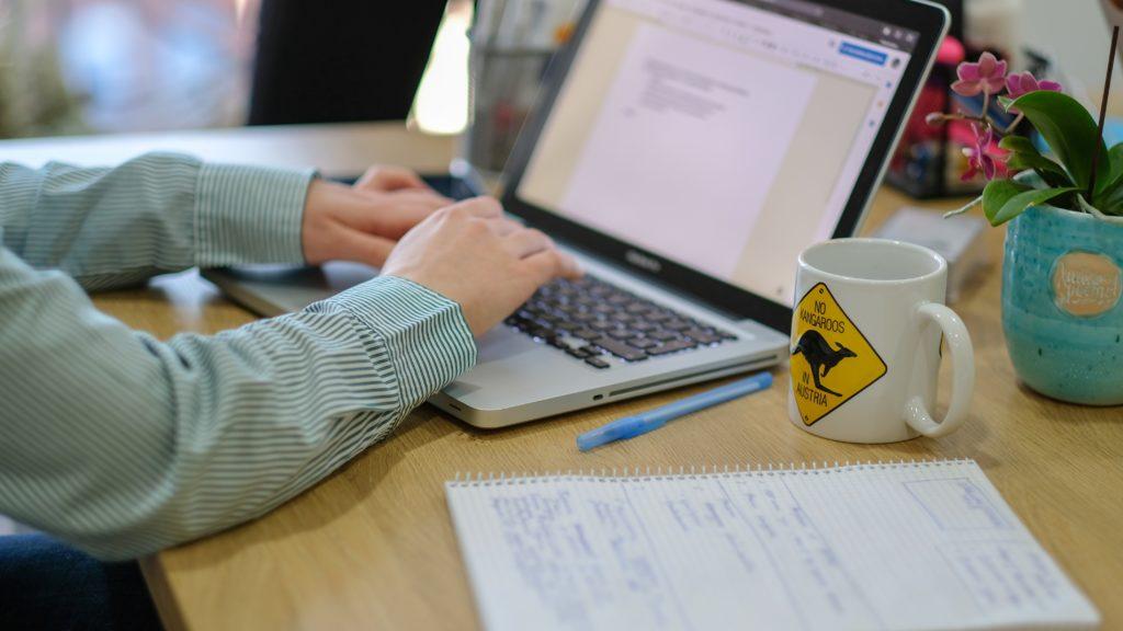 Bild zeigt eine Person, die am Tisch sitzt und einen Laptop benutzt.