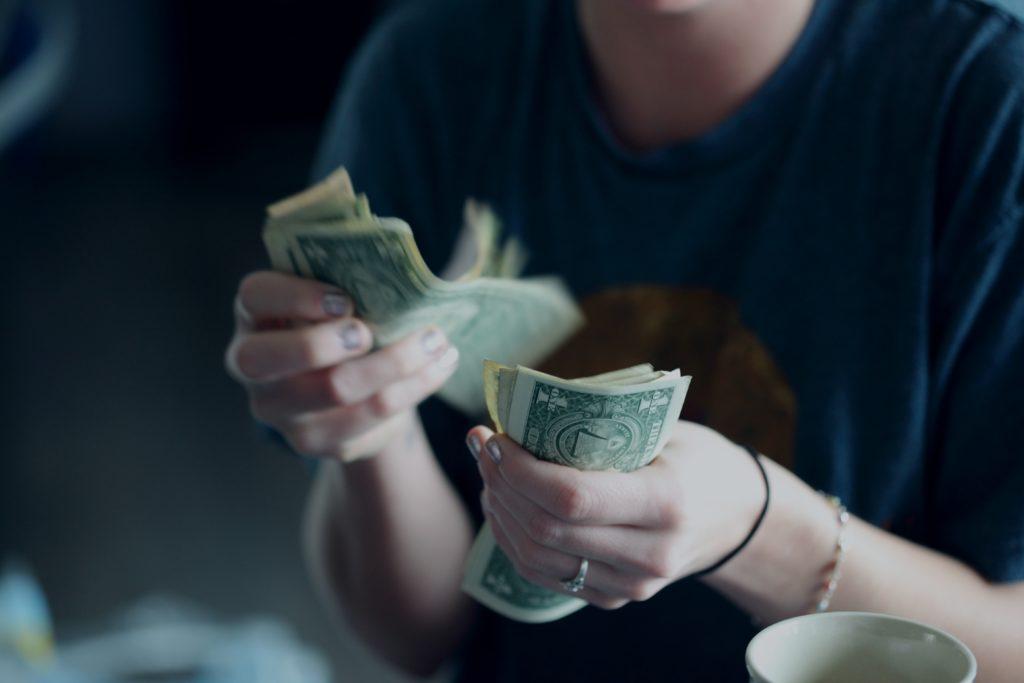Fokusfotografie der Person, die Dollar-Banknoten zählt.