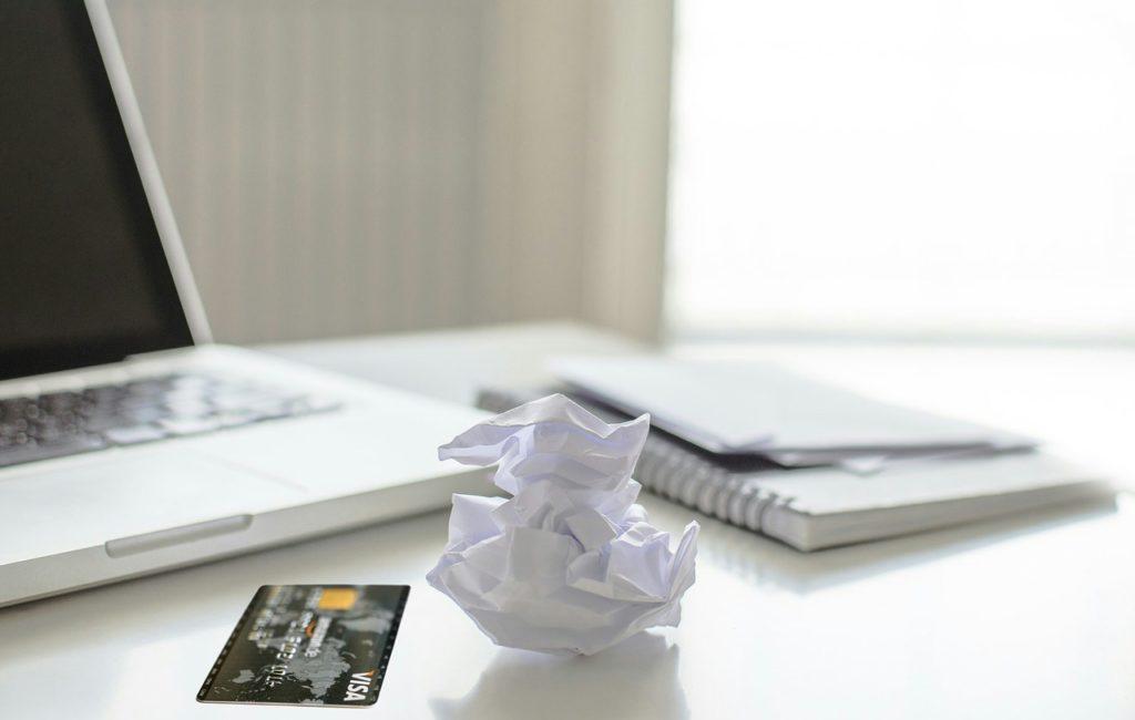 Bild mit einer Kreditkarte, die neben einem Laptop sitzt.
